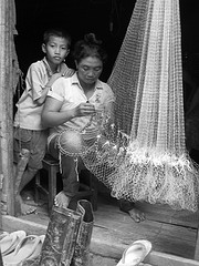Woman repairs a fishing net. by International Rivers