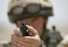 A British soldier aims a Browning 9mm pistol on a shooting range at Basra, Iraq by Defence Images