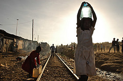 Two young girls carry water on the train tracks that run through the Kibera Slum, by a member of the St. Aloysius Gonzaga High School Journalism Club